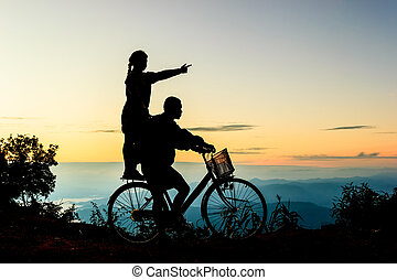 Boy with his sister riding bicycle on sunrise background.Silhouette