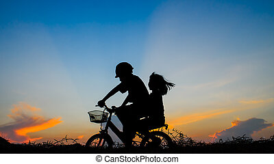 Boy with his sister riding bicycle on sunset background.Silhouet