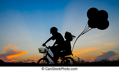 Boy with his sister riding bicycle on sunset background.Silhouette,