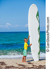 Boy with his surfboard on the beach