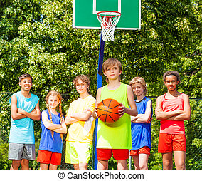 Boy with his team behind during basketball game