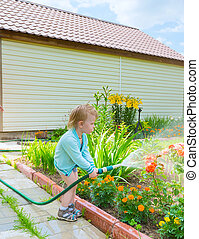 boy with hose - little blond boy pours water from a hose in...