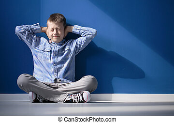 Boy with hypersensitive auditory is covering ears while...