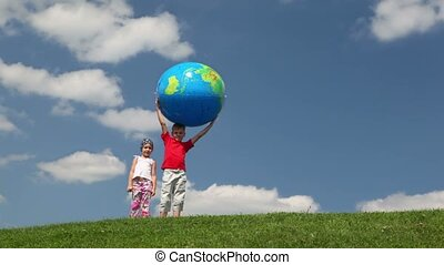 Boy with inflatable ball and girl on meadow