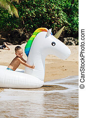Boy with inflatable unicorn on the beach