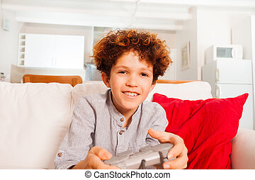Boy with joystick playing video games at home