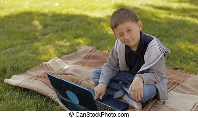 Boy with laptop outdoors,slow motion