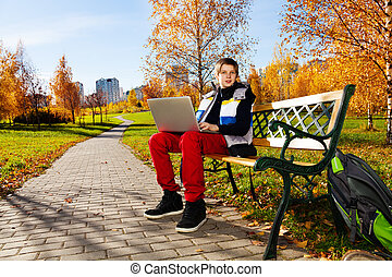 Boy with laptop outside