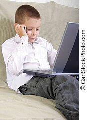 Boy with laptop talking by phone