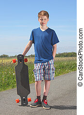 Boy with longboard - Young teenage boy with longboard posing...