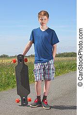 Boy with longboard - Young teenage boy with longboard posing...