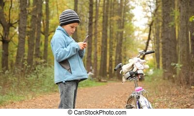 Boy with mobile phone stands near to bicycle in park.
