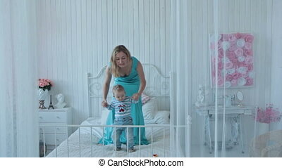 Boy with mother jumping on bed