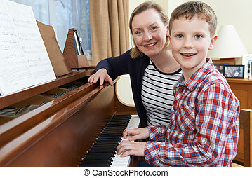 Boy With Music Teacher Having Lesson At Piano