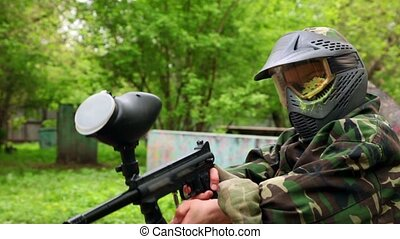 Boy with paint mark on helm holds paintball gun at summer...