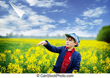 Boy with paper plane in the summer