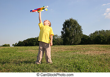 boy with plane on meadow