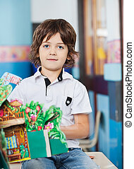Boy With Popup Book Sitting On Desk In Classroom