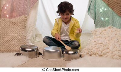 boy with pots playing music in kids tent at home
