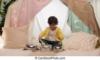 boy with pots playing music in kids tent at home - childhood...