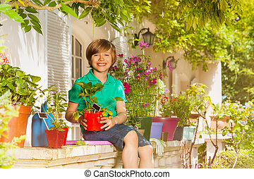 Boy with potted strawberries at balcony garden