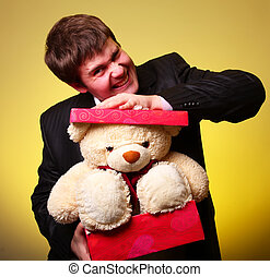 Boy with present box and teddy bear can't select a present...