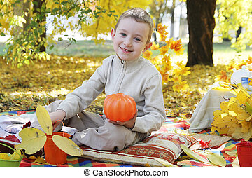 Boy with pumpkin in autumn park