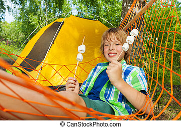 Boy with roasted marshmallow relaxing in a hammock