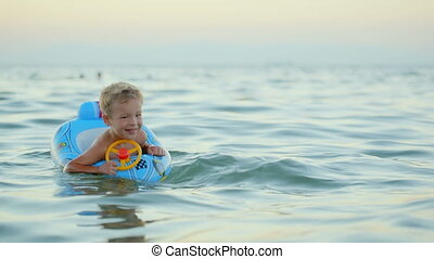 Boy with rubber ring swimming in sea
