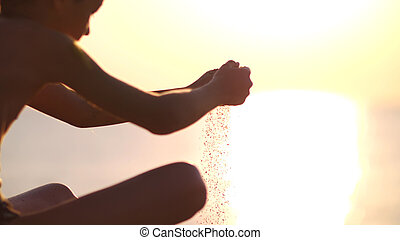 boy with sand falling through her hands on the beach at sunset