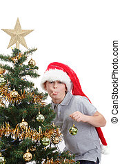 Boy with santa hat sticking out tongue at  the Christmas tree