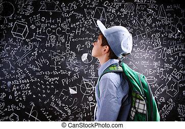 Boy with schoolbag against big blackboard with mathematical...