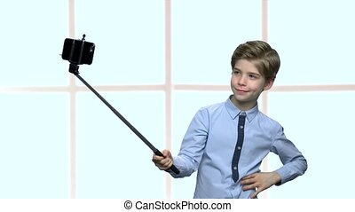 Boy with selfie stick showing fig to camera.