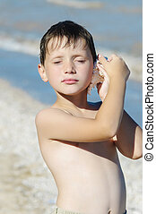 boy with shell on the beach