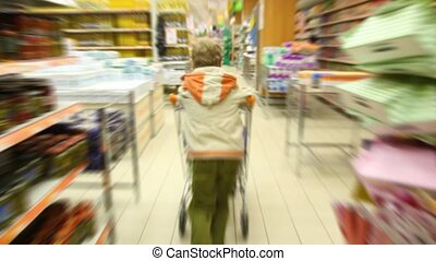 boy with shopping trolley running in supermarket, camera...