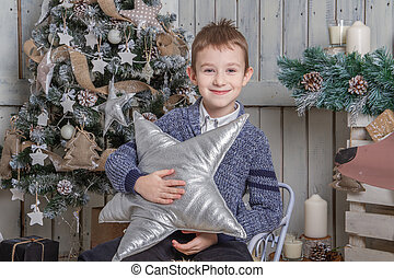 Boy with silver star sitting on sledge under Christmas tree