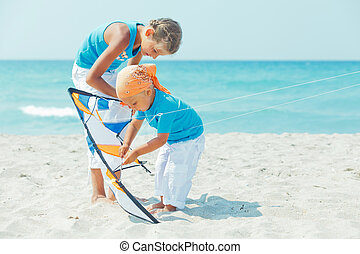boy with sister on beach playing with a kite