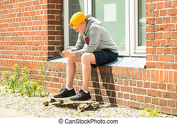 Boy With Skateboard Using At His Mobile Phone