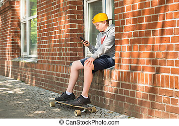 Boy With Skateboard Using  His Mobile Phone