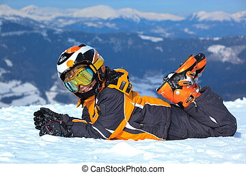 Side view of boy lying in ski clothes with helmet and goggles on snowy Alpine mountain.