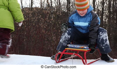 boy with sled ride down mountain, and then girl behind him ...