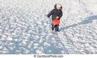 Boy with sled rises to snowy hill, falls, climbs and...
