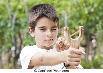 boy with slingshot outdoors