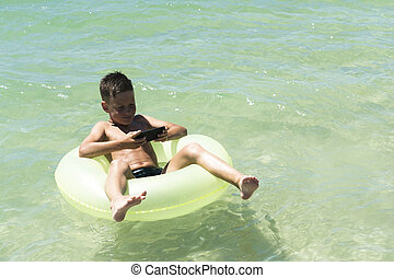 Boy with smart phone on float in the sea