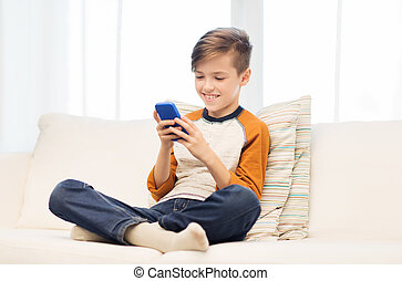 boy with smartphone texting or playing at home - leisure,...