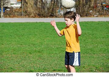Boy with soccer ball - Little boy bouncing soccer ball on...