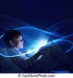 Boy with tablet in his bed