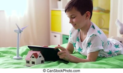 boy with tablet pc and wind turbine toy at home - childhood,...