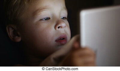 Boy with tablet PC before bedtime - Close-up shot of little...