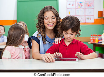 Boy With Teacher Using Digital Tablet